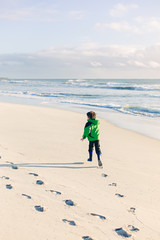 Boy running along wet sand at the beach in winter