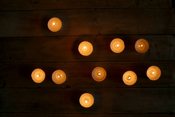 Burning candles  in the darkness. Small round tea light candles on wooden table top view.