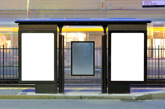 Two Blank Billboards In City Street At Night. Bus Stop Advertising
