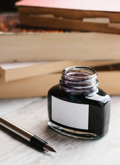 An ink bottle, fountain pen and books.