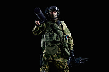 The soldier of the special unit stands in military uniform with a ram on his shoulder and a device for opening the doors.