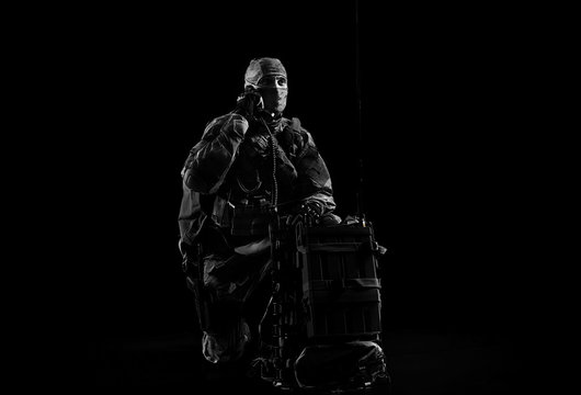 The soldier of the special unit in military uniform sits near the satellite communications apparatus and causes support.