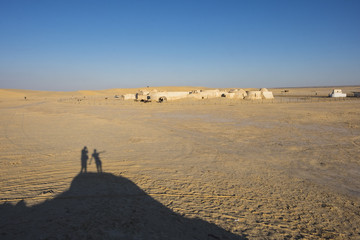 Shadow of two youngs in the Sahara desert.