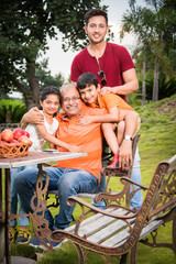 Indian father with kids, young indian girl and boy embracing Father sitting over lawn chair - Happiness concept and asian family