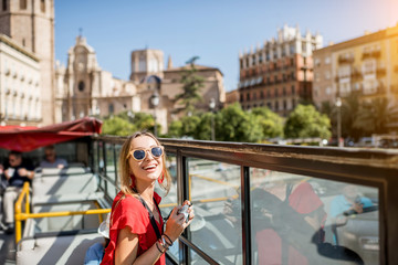 Fototapeta Young happy woman tourist in red dress having excursion in the open touristic bus in Valencia city, Spain