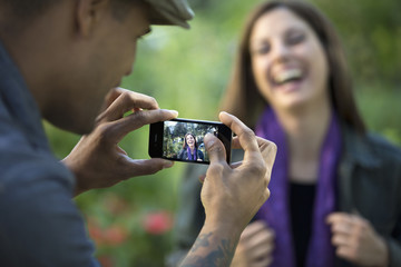 Happy multiethnic couple taking photos with cell phone