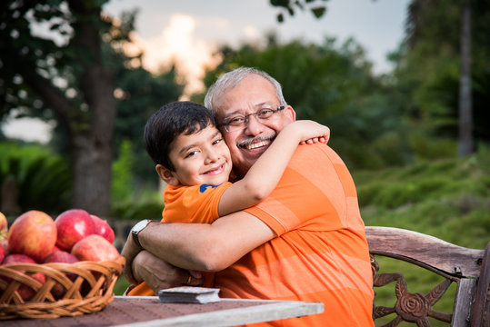 Young Indian boy embracing grandfather sitting in garden, Portrait of Indian grandfather and Grandchild