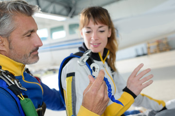 Instructor showing equipment to skydiver