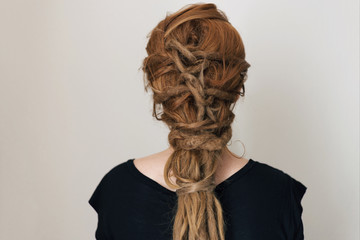Ginger woman with dreadlocks. Interesting hairstyle. Braid with knots