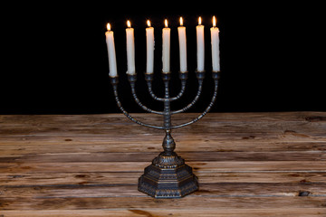 Ancient ritual candle menorah on a black background