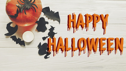 happy halloween text. pumpkin with witch ghost bats and spider black decorations on white wooden background top view with space for text. seasonal greetings, holiday celebration