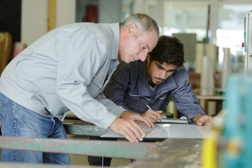 two workers choosing pvc aluminium window profile at stand
