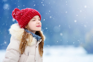 Adorable little girl catching snowflakes with her tongue in beautiful winter park. Cute child playing in a snow.