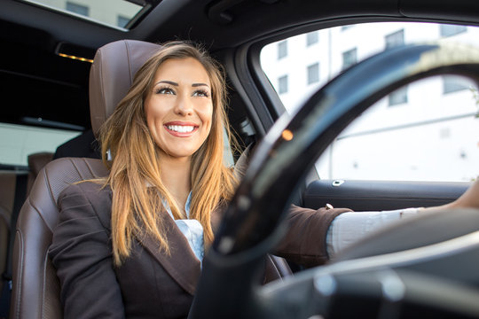 Beautiful businesswoman smiling in a car