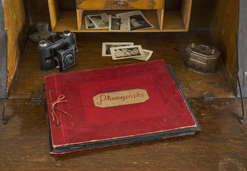 Old camera and photo album on a desk