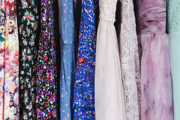Selection of cute summer dresses hanging in a wardrobe