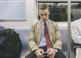 Male Student-Intern Using Smartphone in Train of Subway Transportation of New York