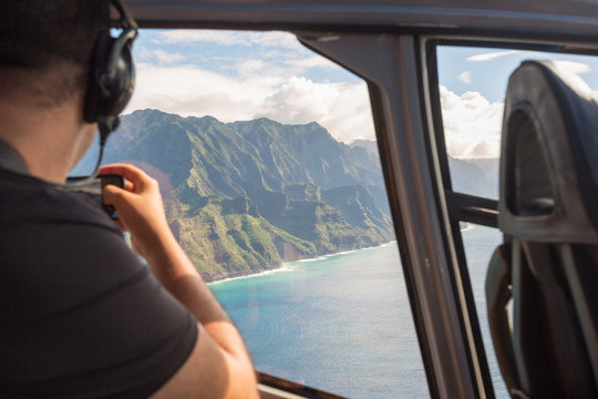 Napali coast from a helicopter with a tourist taking pictures