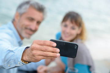 Man and lady photographing themselves with cellphone