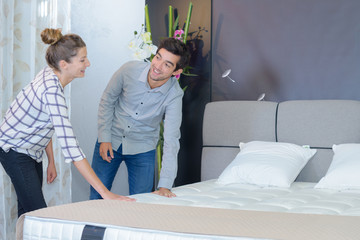 cheerful young couple choosing furniture in store