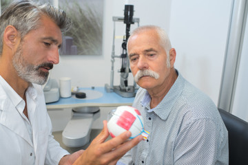 doctor showing senior patient the eye models anatomy