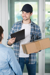 smiling delviery man holding parcel and clipboard