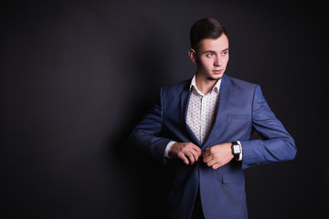 Successful young businessman in business suit and white shirt and fashionable clock on hand on a black background. Stylish man. Men's professions