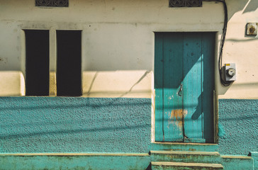 Front of a old antique traditional house with vibrant blue/turquoise facade