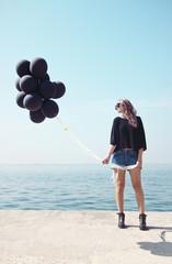 Beautiful woman holding black balloons