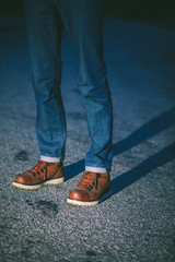 Man in brown boots standing on the street at night