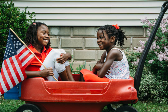 Two Smiling African-American Girls in USA Flag Themed Outfits in a Wagon