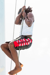 Black man climbs the mast, Saona island, Dominican Republic. Close-up. Vertical.