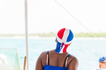 The girl in a headdress, Saona island, Dominican Republic. Copy space for text. Back view.