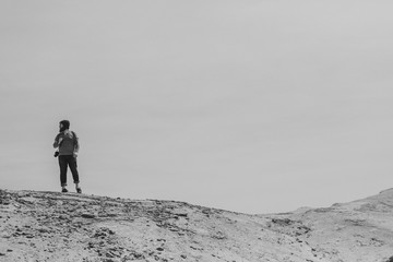 Man standing on top of a sand dune