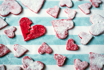 Close-up of red heart shaped cookies placed on table cloth