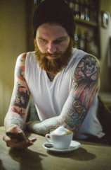 Hipster tattooed man sitting in a cafe