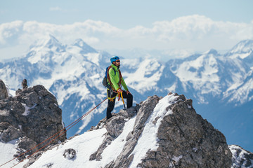 male mountaineer on top of a summit in the austrian alps
