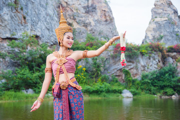 Beautiful asian woman wearing Thai ancient traditional costume dancing and smiles near by the river