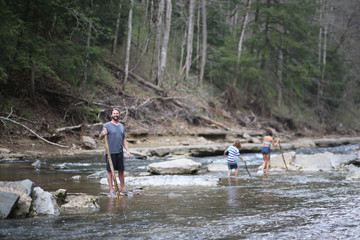 A Man And His Children Hiking Through A River Bed