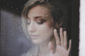 Beautiful young  woman standing at the window watching the rain