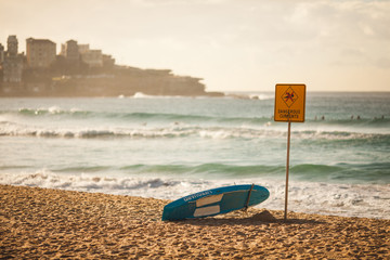 Dangerous currents sign and lifeguard board on the beach