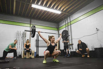 Group of workout friends cheering on woman as she lifts weights