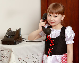 A little girl is ringing on the old phone.