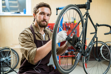 Portrait of bearded young repairman sitting on haunches and looking at camera while repairing bicycle at spacious workshop
