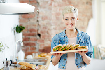 Happy girl holding board with appetizing sandwiches in the kitchen