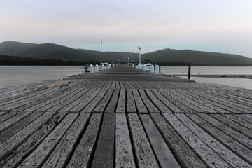 A long weathered pier reaches out to the early dawn light