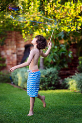 Boy playing with bubbles in a garden in summer