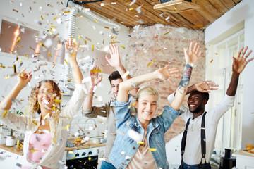 Ecstatic friends raising hands during dance under confetti fall