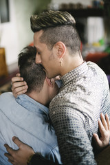 Young gay couple together at home