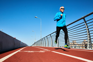 Low angle view of concentrated senior sportsman jogging outdoors and enjoying sunny warm day, full length portrait